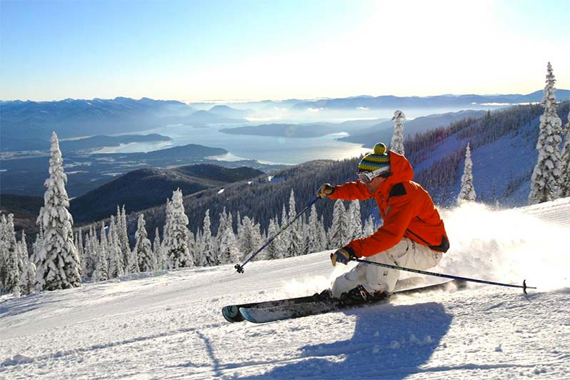 Man skiing down a snowy mountain with a lake in the background