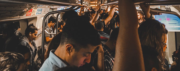 Crowded train with people holding onto rail