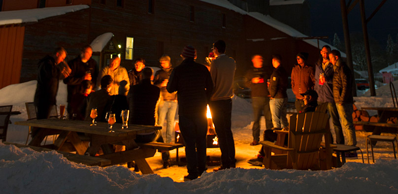 A group of adults standing outside around a fire pit at night during the Kochava Mobile Summit event.