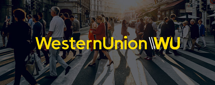 People crossing a busy street and Western Union colored logo